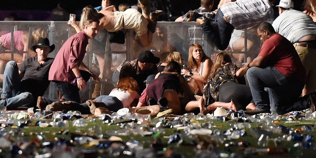 People scramble for shelter at the Route 91 Harvest country music festival after gun fire was heard on October 1, 2017 in Las Vegas, Nevada.