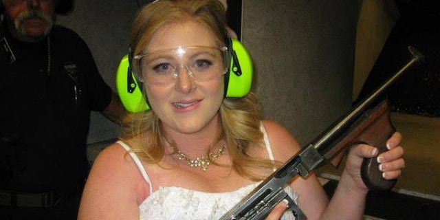 "July 28, 2012: Lindsae MacDuff holds an automatic weapon at the Gun store in Las Vegas after her ""shotgun wedding."""