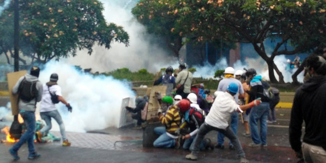 Demonstrators throw rocks and Molotov cocktails against police in a riot against Nicolas Maduro.