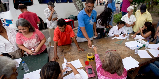 Voters register with members of the ruling United Socialist Party before proceeding to a polling post to vote in presidential elections in Valencia, Venezuela, Sunday, May 20, 2018.