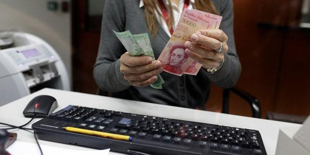 A bank teller counts bolivar banknotes at a Banco de Venezuela branch in Caracas, Venezuela January 16, 2017. REUTERS/Marco Bello - RTSVRHG