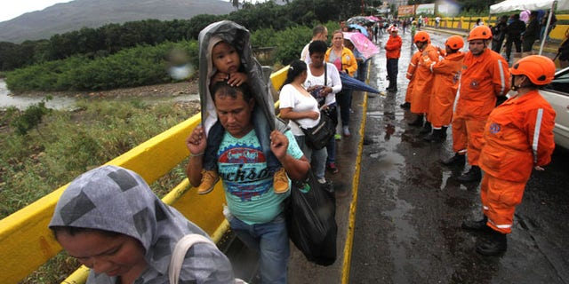 Venezuelans cross the Simon Bolivar bridge linking San Antonio del Tachira, in Venezuela with Cucuta, Colombia in order to buy supplies, on July 16, 2016.Thousands of Venezuelans crossed into the Colombian city of Cucuta to buy food and medicine, taking advantage of another brief opening in the border that's been closed nearly a year. Caracas authorized the temporary opening a week after some 35,000 Venezuelans poured across the border during a 12-hour opening of the pedestrian bridge.  / AFP / GEORGE CASTELLANOS        (Photo credit should read GEORGE CASTELLANOS/AFP/Getty Images)