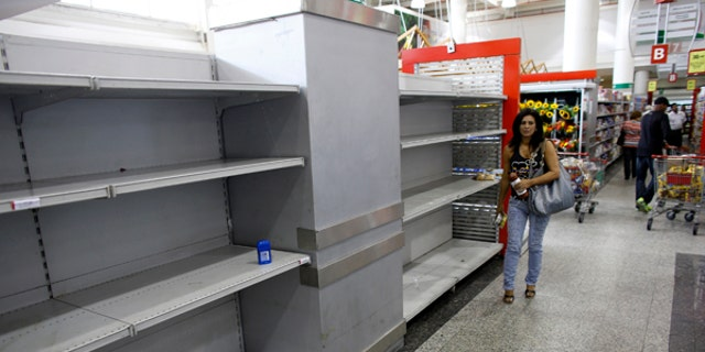 A woman walks past an empty section where toilet paper should be on display in a super market in Caracas.