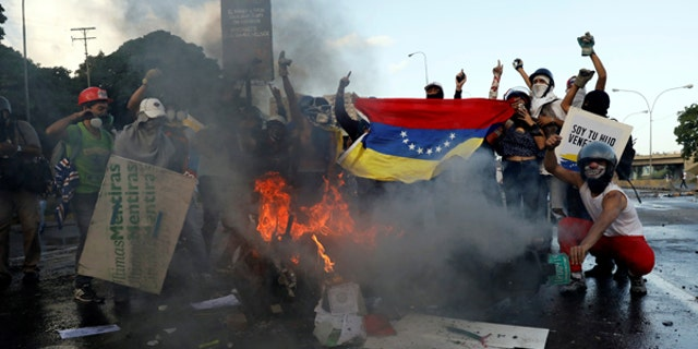 Opposition supporters hold a Venezuelan national flag in front of a burning riot security force motorcycle during clashes at a rally against Venezuelan President Nicolas Maduro's government in Caracas, Venezuela June 22, 2017. REUTERS/Carlos Garcia Rawlins - RTS189Z3