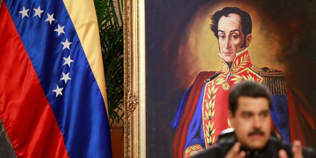A painting of South American independence leader Simon Bolivar is seen as Venezuela's President Nicolas Maduro talks to the media during a news conference at Miraflores Palace in Caracas, Venezuela June 22, 2017.