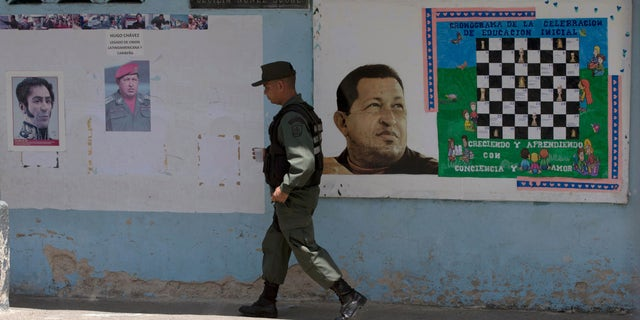 A Bolivarian National Guards officer walks near images of the late Venezuelan President Hugo Chavez and Independence hero Simon Bolivar, left, at a poll station in Caracas, Venezuela, Sunday, May 17, 2015. Venezuelans are voting to select the opposition leaders who will run against the ruling socialist partyâs candidates in upcoming legislative elections thought to be government criticsâ first chance at an electoral victory in years. (AP Photo/Fernando Llano)
