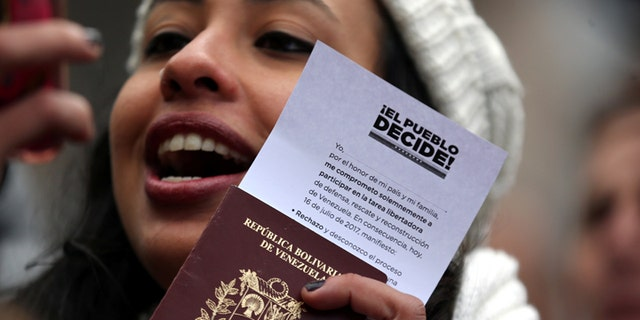 A Venezuelan woman shows her passport and a ballot certificate after casting her vote during an unofficial plebiscite against President Nicolas Maduro's government in Buenos Aires, Argentina, July 16, 2017. REUTERS/Marcos Brindicci - RC1C40A2CCC0