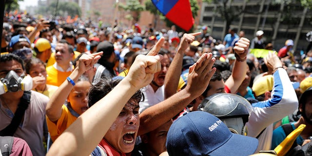 Demonstrators react during an opposition rally in Caracas, Venezuela April 4, 2017. REUTERS/Carlos Garcia Rawlins - RTX3422D