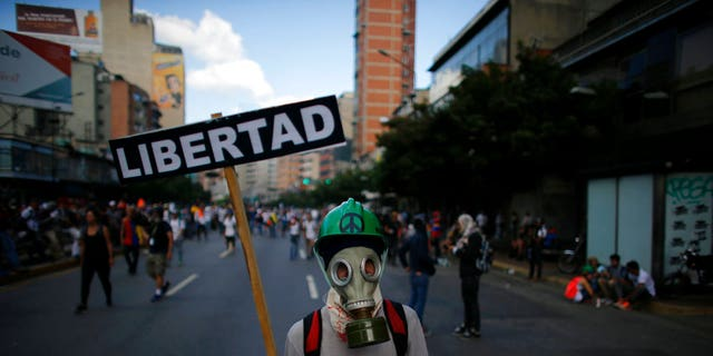 "A masked protester holds a placard that reads in Spanish: ""Liberty"" during clashes with government security forces in Caracas, Venezuela, Saturday, May 20, 2017."
