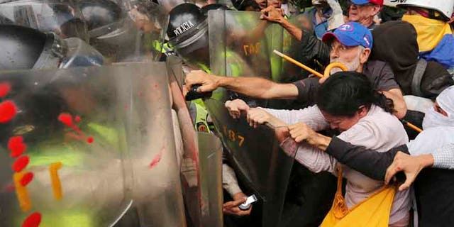 Anti-government protesters scuffle with police blocking older Venezuelans from marching to the Ombudsman's Office in protest of President Nicolás Maduro in Caracas, Venezuela, Friday, May 12, 2017.