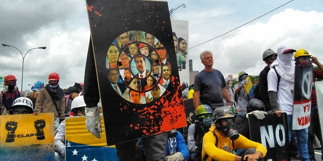Young man observes the security forces with a shield that has the faces of high government officials.