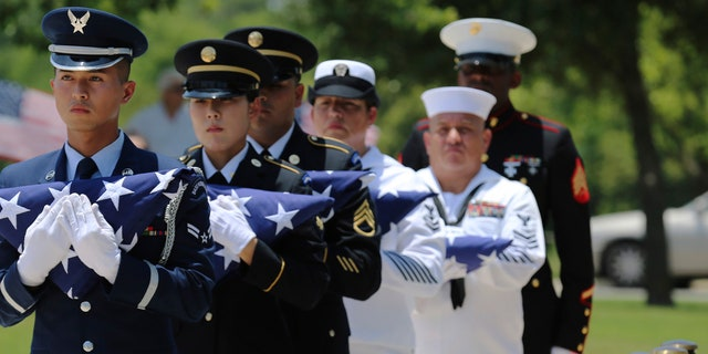 In this Friday, June 1, 2018 photo, military service members with the Armed Services Honor Guard prepare to present folded flags as Fort Sam Houston National Cemetery and the Missing In America Project conduct a military burial service for the cremated remains of eight unclaimed veterans in San Antonio.