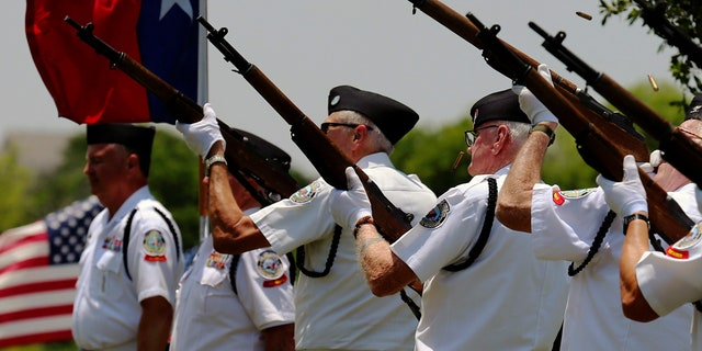 Shell casings eject from the rifles of the Fort Sam Houston Memorial Services Detachment Honor Guard as they fire three volleys during a burial service by Fort Sam Houston National Cemetery and the Missing In America Project for the cremated remains of eight unclaimed veterans in San Antonio, June 1, 2018.