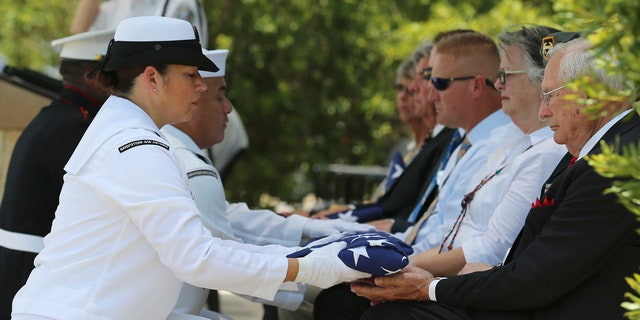 Navy Reservist Second Class Petty Officer Linda Villalobos presents a folded U.S. Flag to an official as Fort Sam Houston National Cemetery and the Missing In America Project conduct a military burial service for the cremated remains of eight unclaimed veteran in San Antonio.
