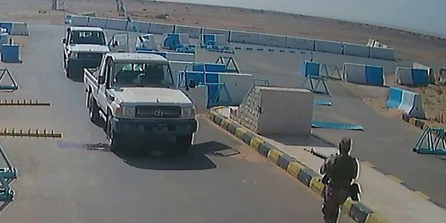 A still image taken from the surveillance video shows al-Tuwayha charging at the American soldiers with his gun drawn.
