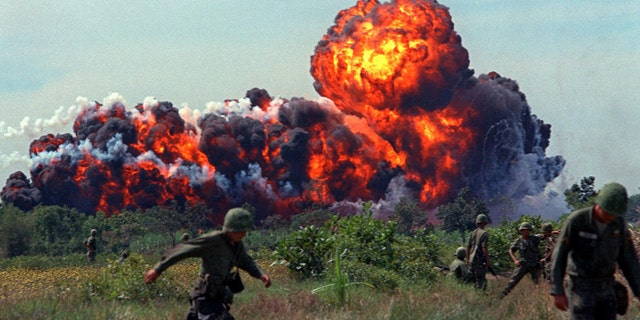 Napalm strike erupts in fireball near U.S. troops on patrol in 1966, South Vietnam. A few million people died during the war.