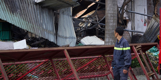 May 14, 2014; A man looks at the damaged building of Taiwanese bicycle factory Tan Than in Di An Town, Binh Duong Province, Vietnam.  (AP)