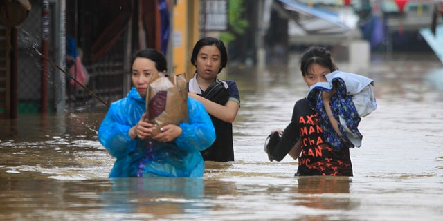 People wade through flooded street of Hoi An ancient town, Vietnam, Monday, Nov. 6, 2017.