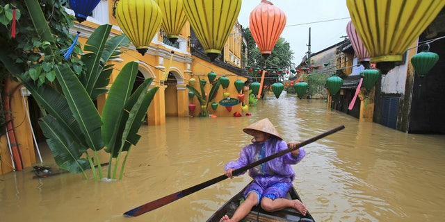 Nguyen Thi Vui paddles her boat in the flooded streets of Hoi An, Vietnam, Monday, Nov. 6, 2017.