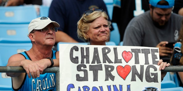 Carolina Panthers fans hold a sign as they watch the Panthers and Vikings warm up.