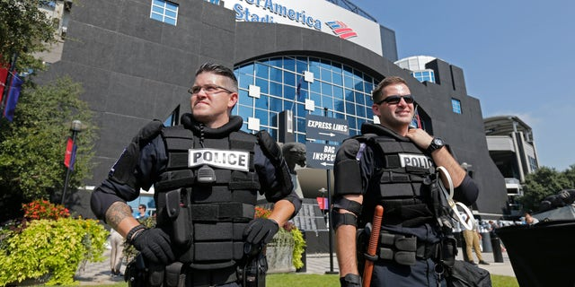 Charlotte-Mecklenburg Police officers stand guard outside Bank of America Stadium.