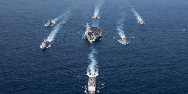 The Nimitz-class aircraft carrier USS Carl Vinson (CVN 70), the Arleigh Burke-class guided-missile destroyer USS Wayne E. Meyer (DDG 108) and the Ticonderoga-class guided-missile cruiser USS Lake Champlain (CG 57) in a photo exercise with Japan Maritime Self-Defense Force destroyers.
