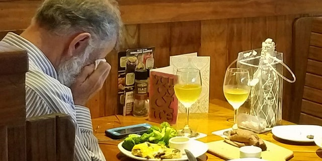 A man seen sitting at a restaurant dining with his wife's ashes.