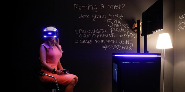 File photo: A woman tries on earphones and a headset used for virtual reality at the Venice Virtual Reality a competition during 74th Venice Film Festival in Venice, Italy, August 29, 2017. (REUTERS/Alessandro Bianchi)