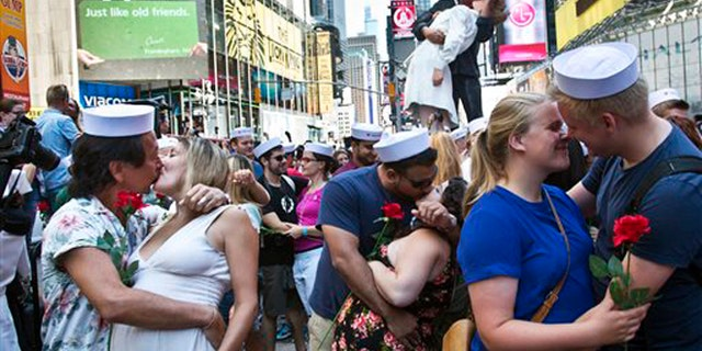 Friday Aug.14, 2015L Married couple Kenji and Kristen Kawasaki, far left, join others as they re-enact the iconic 1945 Alfred Eisenstaedt kiss photo in New York's Times Square. Dozens of couples gathered to re-enact the famous kiss that celebrated the end of World War II.