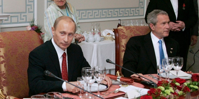 """FILE - In this Monday, July 19, 2006 file photo, Russian President Vladimir Putin, left, and U.S. President George W Bush attend a working dinner with the other leaders of the G8 nations, as Russian businessman Yevgeny Prigozhin stands on the right, in St. Petersburg, Russia. While Russian officials have denigrated a U.S. indictment charging 13 Russians with meddling in the 2016 U.S. presidential vote through an elaborate social media campaign, former Internet trolls employed at the same facility see them as well-grounded. The indictment alleged that Yevgeny Prigozhin _ a wealthy entrepreneur and restaurateur dubbed """"Putin's chef"""" _ funneled money to set up the troll factory that sent operatives to the United States, created fictitious social media accounts and used them to spread tendentious messages. (Sergei Zhukov, Sputnik, Kremlin Pool Photo via AP, file)"""