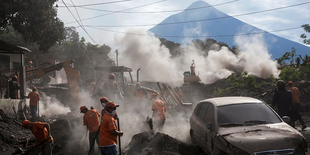 "Rescue workers remove piles of ash spewed by the Volcan de Fuego, or ""Volcano of Fire,"" eruption, in El Rodeo, Guatemala on Wednesday."