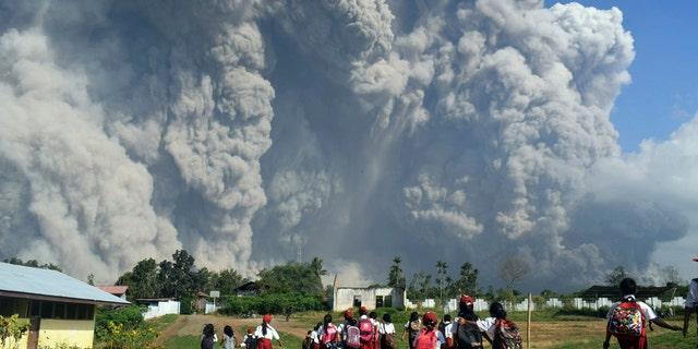 School children walk as Mount Sinabung erupts in Karo, North Sumatra, Indonesia, Monday, Feb. 19, 2018.