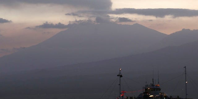 FILE - In this Sunday, July 12, 2015 file photo, a ferry boat crosses the Bali Strait to carry Indonesians to Ketapang port, East Java, from Gilimanuk port, West Bali, Indonesia as Mount Raung spews volcanic smoke. Eruptions at two volcanoes have caused closures at three Indonesian airports, including one serving the country's second-largest city. Mount Raung on the main island of Java blasted ash and debris up to 2,000 meters (6,560 feet) into the air after rumbling for several weeks. Gamalama mountain in eastern Indonesia erupted Thursday after months of quiet. (AP Photo/Firdia Lisnawati, File)