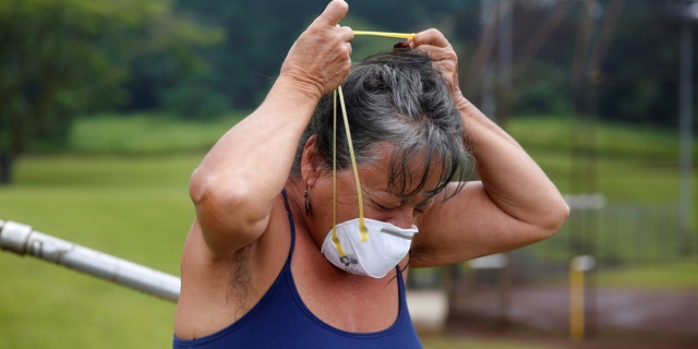 Laura Rillamas, of Orchidland, puts on a dust mask to protect herself from volcanic emissions in Keaau during ongoing eruptions of the Kilauea Volcano in Hawaii.