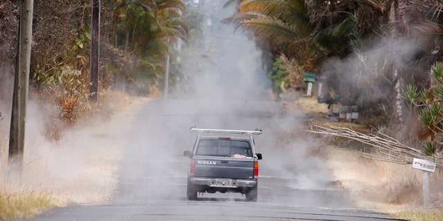 A driver steers through volcanic gasses in the Leilani Estates subdivision during ongoing eruptions of the Kilauea Volcano in Hawaii, U.S., May 13, 2018.