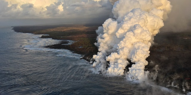 A laze plume rises where lava pours into the sea from fissure 8 on Hawaii's Big Island.