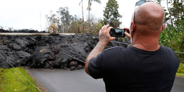 A resident of the Leilani Estates subdivision takes photos of a lava flow near his home.