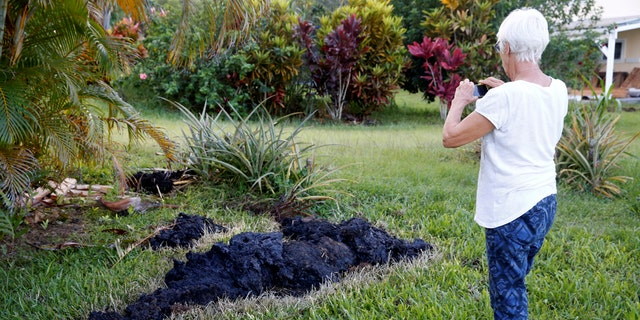 Patricia Spinoza, of Puna, takes a photo of lava on a lawn on the outskirts of Pahoa.