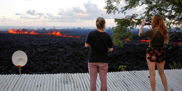 Jolon Clinton, 15, left, and her sister, Halcy, 17, take photos of a fissure near their home on the outskirts of Pahoa.
