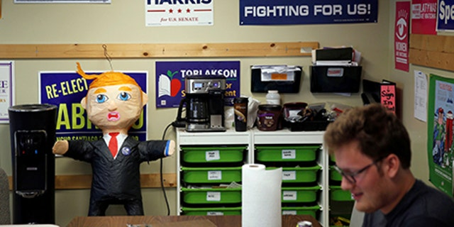 A pinata of Republican Presidential Candidate Donald Trump stands in front of various campaign signs decorating a wall as members of the Democratic Party of Orange County prepare to canvass a neighborhood in Orange, California May 15, 2016. Picture taken May 15, 2016.  REUTERS/Patrick T. Fallon - RTSEKHI