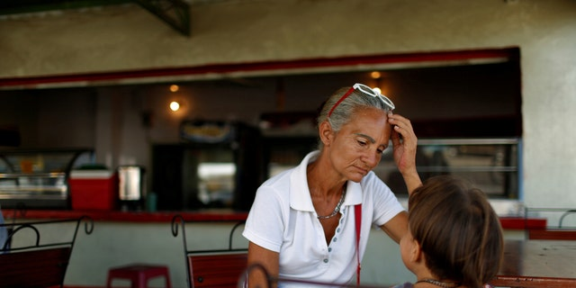Zulay Pulgar, 43, in a coffee shop with her son Emmanuel, 4, after standing in line to buy cement in a hardware store in Punto Fijo, Venezuela November 17, 2016.