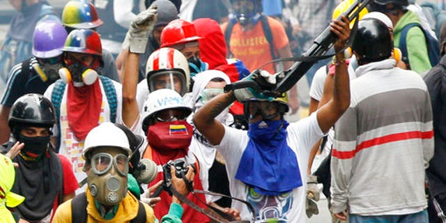 An anti-government demonstrator shows a shotgun taken from security forces during clashes in Caracas, Venezuela, Monday, May 8, 2017,
