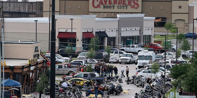 In this May 17, 2015 file photo, authorities investigate a shooting in the parking lot of Twin Peaks restaurant in Waco, Texas.