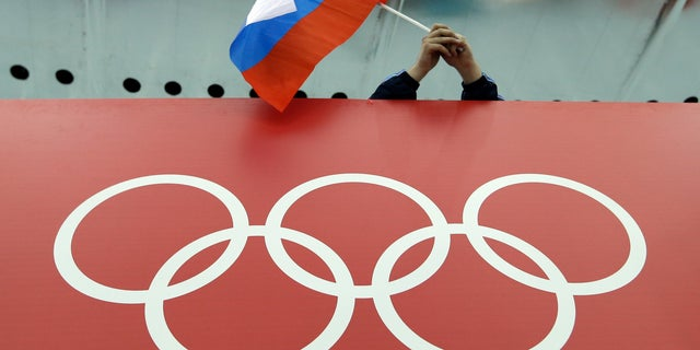 Feb. 18, 2014: A Russian skating fan holds the country's national flag over the Olympic rings before the start of the men's 10,000-meter speedskating race at Adler Arena Skating Center during the 2014 Winter Olympics in Sochi, Russia. (AP)
