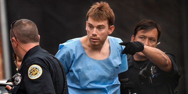 Travis Reinking, suspected of killing four people in a late-night shooting at a Waffle House restaurant, is escorted into the Hill Detention Center in Nashville.