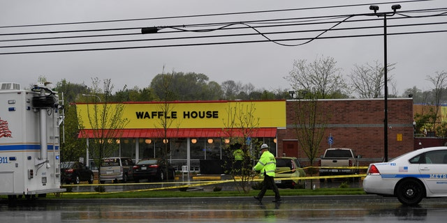 Metro Davidson County Police inspect the scene of a fatal shooting at a Waffle House restaurant.