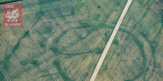 Cropmarks of a large prehistoric enclosure in Wales' Vale of Glamorgan, with the faint footings of a probable Roman villa within (Crown Copyright RCAHMW)
