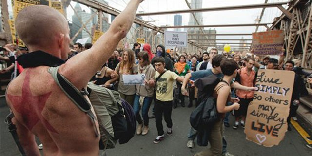A large group of protesters affiliated with the Occupy Wall Street movement attempt to cross the Brooklyn Bridge, effectively shutting parts of it down, Saturday, Oct. 1, 2011 in New York.