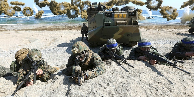 Marines of the U.S., left, and South Korea wearing blue headbands on their helmets, taking positions after landing on a beach during a joint military combined amphibious exercise in Pohang, South Korea.