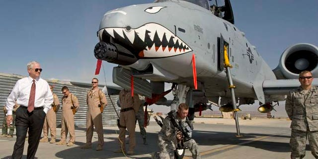 """FILE 2008: Then-US Secretary of Defense Robert Gates, left, greets the crew and looks over an A-10 """"Warthog,"""" a close support aircraft, during an unannounced visit to Bagram Airfield."""